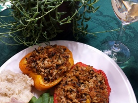 savory stuffed peppers on a plate with a hunk of crusty bread and a glass of wine